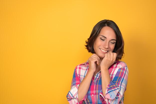 Affascinante donna che esprime tenerezza e dire addio in camicia a quadri su uno sfondo giallo con copia spazio. espressioni facciali, emozioni, sentimenti.
