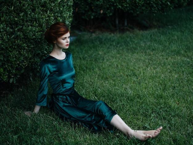 Affascinante donna in abito verde si siede sul prato verde cespuglio di lusso.