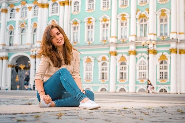 Un'affascinante donna in jeans siede sull'asfalto nella piazza del palazzo a san pietroburgo