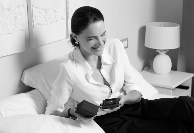 Affascinante donna giace su un letto in una camera da letto e tiene una scatola con un anello.