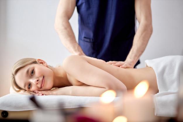 Affascinante donna sdraiata sulla pancia che riceve un massaggio termale sulla schiena da un massaggiatore maschio bionda signora di ca...