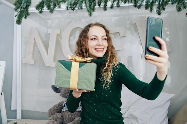 Affascinante donna che fotografa con regalo