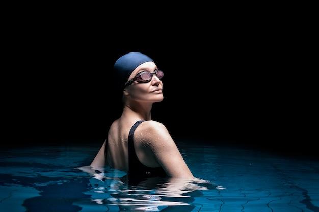 Affascinante donna in posa in piscina. vista posteriore.