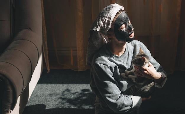 Affascinante donna seduta sul pavimento con un gatto alla luce di una lampada che indossa un asciugamano sulla testa e una maschera facciale nera