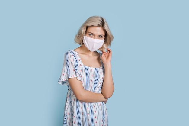Affascinante donna che indossa un abito estivo blu su una parete di studio che indossa una maschera medica sul viso
