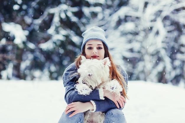 Affascinante donna con il suo cane nella foresta invernale