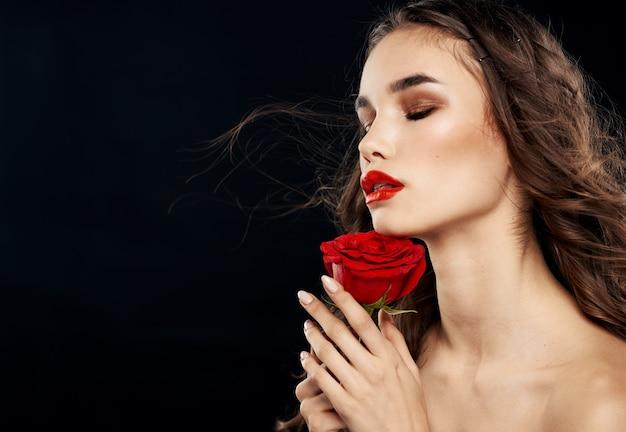 Affascinante donna con rosa rossa ombretto trucco luminoso sfondo nero