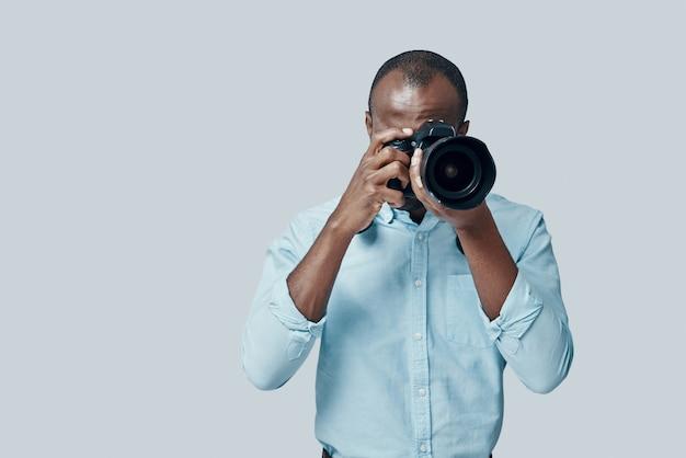 Affascinante giovane africano che scatta una foto usando la fotocamera digitale mentre si trova contro il muro grigio