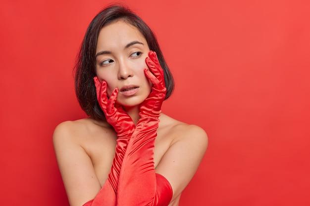 Affascinante giovane donna asiatica con i capelli scuri tiene le mani sul viso sembra teneramente da parte sta con le spalle nude indossa guanti lunghi posa contro il muro rosso vivo vivido