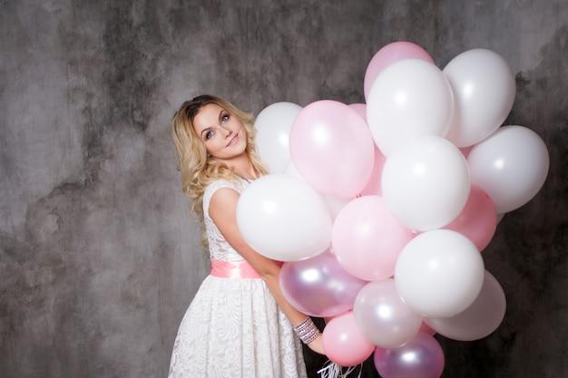 Affascinante giovane bionda in abito bianco con palloncini rosa, alla festa.