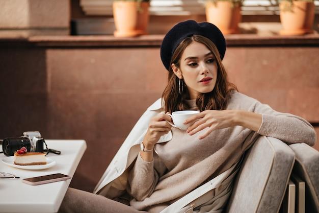 Affascinante giovane bruna con berretto scuro, maglia beige e trench, fare colazione, bere caffè, mangiare cheesecake, sulla terrazza del caffè della città durante la giornata di sole