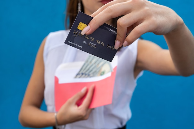 Affascinante giovane signora di affari che tiene i dollari in una busta e una carta di credito per lo shopping