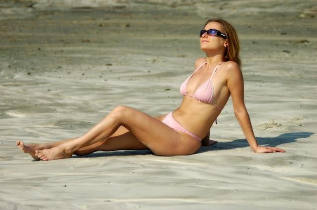 Affascinante giovane donna contenta in un costume da bagno rosa si siede su una spiaggia sabbiosa e prende il sole al sole, soleggiata calda giornata estiva calda durante le vacanze in mare