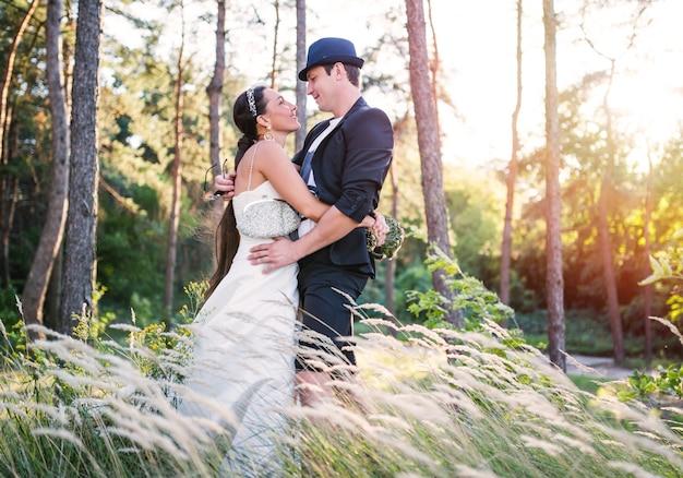 Affascinante giovane coppia appena sposata bella donna in abito bianco e sposo in abito e cappello in posa in un campo con erba alta. sfondo della foresta in una soleggiata giornata estiva calda