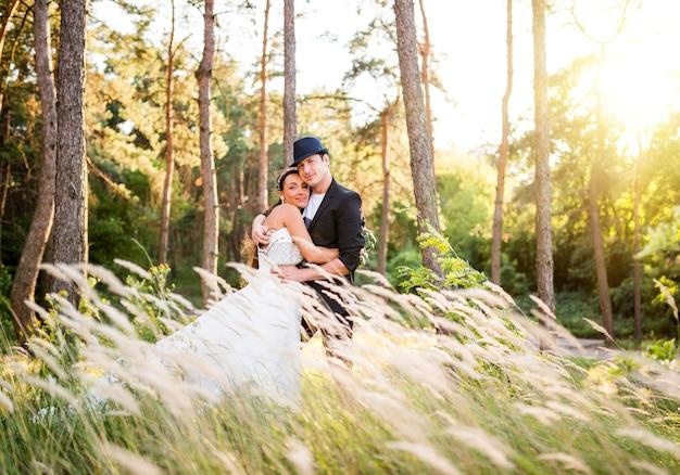 Affascinante giovane coppia appena sposata in posa in un campo con erba alta
