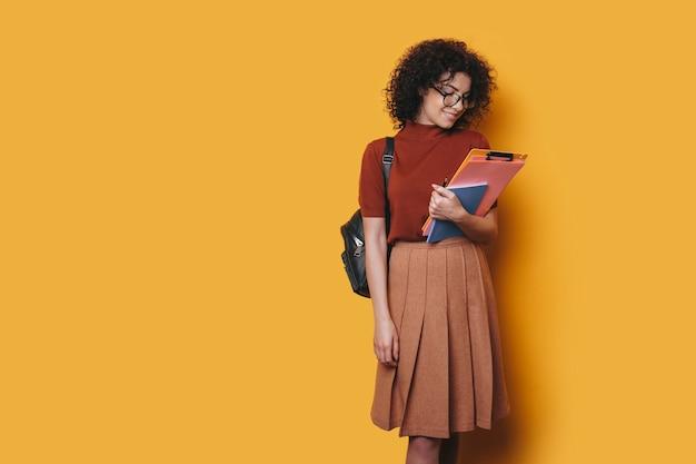 Affascinante giovane studentessa riccia guardando i suoi libri di studio isolati su sfondo giallo.