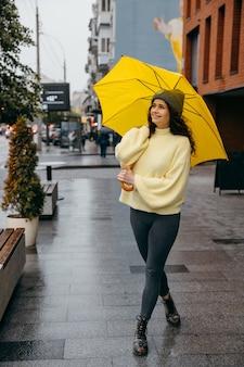 Affascinante giovane donna riccia usa l'ombrello giallo sulla strada della città di megapolis in una giornata piovosa