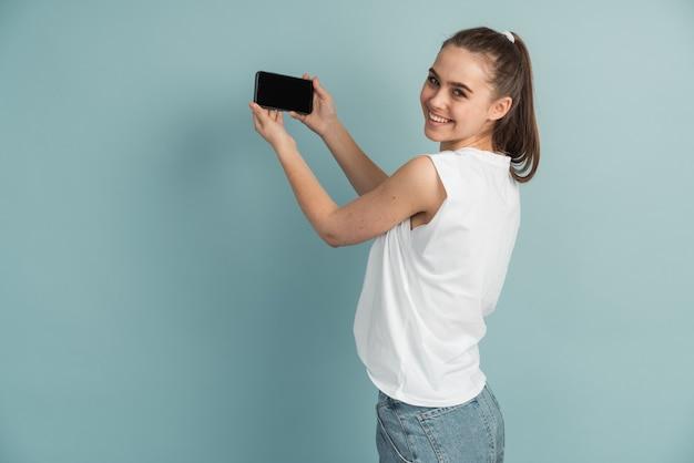 Affascinante ragazza che tiene un telefono nelle sue mani