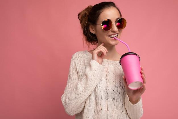 Affascinante giovane donna bruna felice che indossa vestiti alla moda
