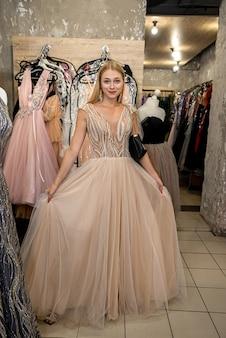 L'affascinante giovane donna ha scelto l'abito da sera perfetto in un negozio di abbigliamento e vi posa. concetto di acquisto