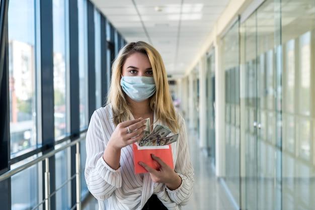 Affascinante giovane donna in una maschera medica che tiene una busta con soldi nel centro commerciale. concetto di finanza