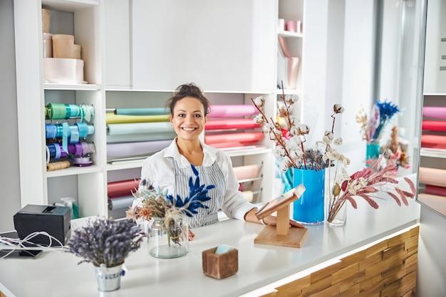 Affascinante giovane donna in posa in un negozio di fiori