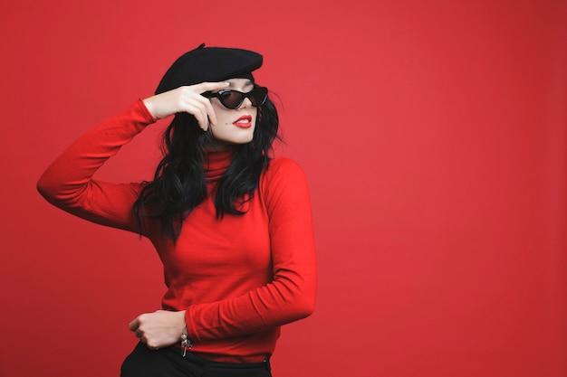 Affascinante giovane signora in abito alla moda in posa per la fotocamera e distogliere lo sguardo mentre si trovava su sfondo rosso vivace