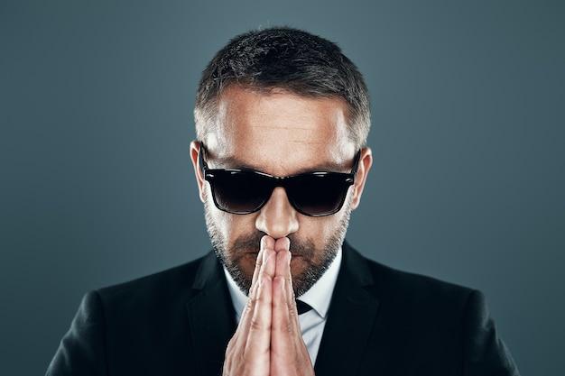 Affascinante giovane in abito completo e occhiali che tiene le mani giunte mentre si trova in piedi su uno sfondo grigio