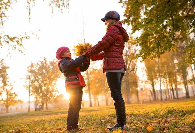 Affascinante giovane madre e figlia che ballano mentre camminano in un caldo parco autunnale in un parco soleggiato con un mazzo di foglie d'acero gialle. concetto di tradizione familiare