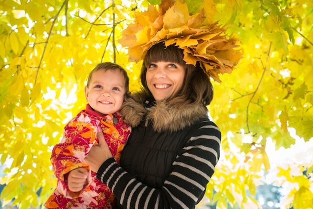 Affascinante giovane madre tiene tra le braccia una graziosa bambina con una ghirlanda di foglie d'autunno di acero giallo in testa mentre cammina nel parco. concetto di autunno