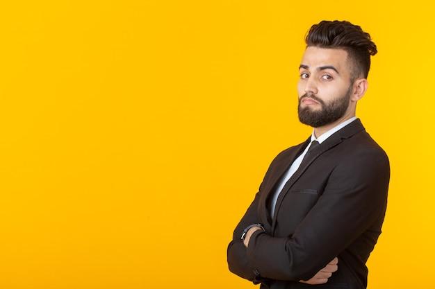 Affascinante giovane uomo d'affari sicuro di sé che indossa abiti formali in posa su uno sfondo giallo con