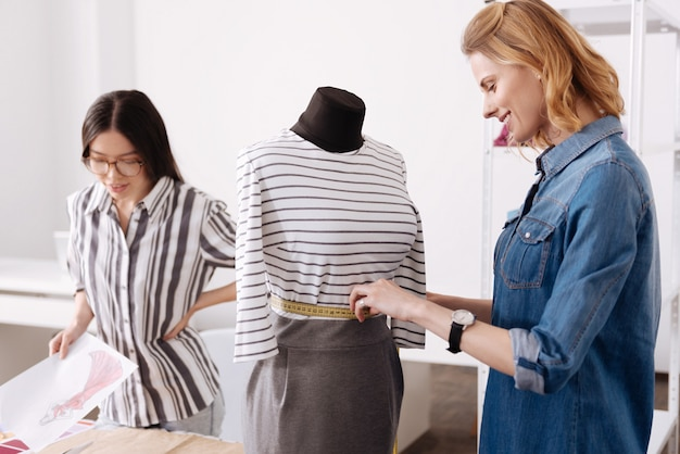 Affascinante giovane sarto che misura la vita di un vestito appeso a un manichino e sembra soddisfatto del risultato, mentre il suo collega guarda uno schizzo di un vestito