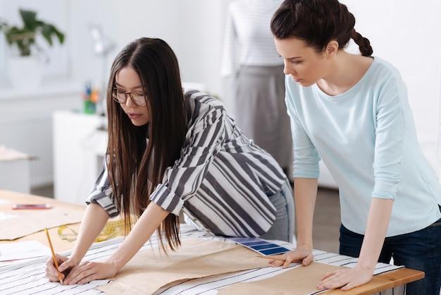 Affascinante giovane sarta che mostra alla sua collega come tracciare motivi su tessuti a righe.