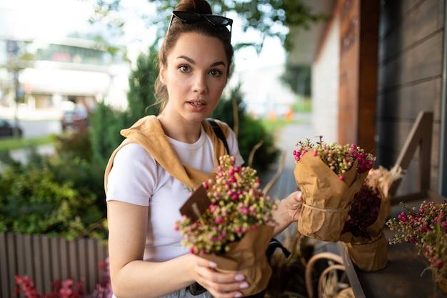Affascinante giovane donna acquisto di fiori al negozio estivo giardino.