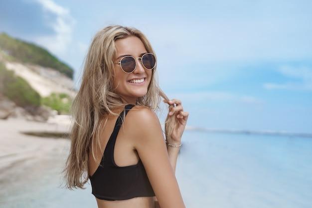 Affascinante giovane donna che gode delle vacanze estive nella soleggiata spiaggia sabbiosa