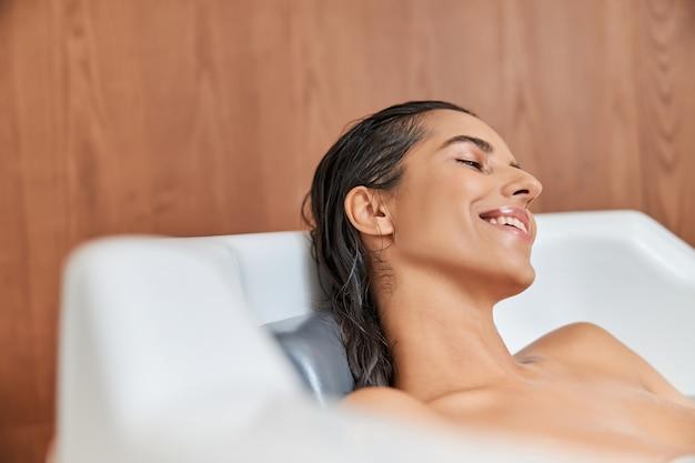 Affascinante giovane donna che si rilassa nella vasca da bagno a casa