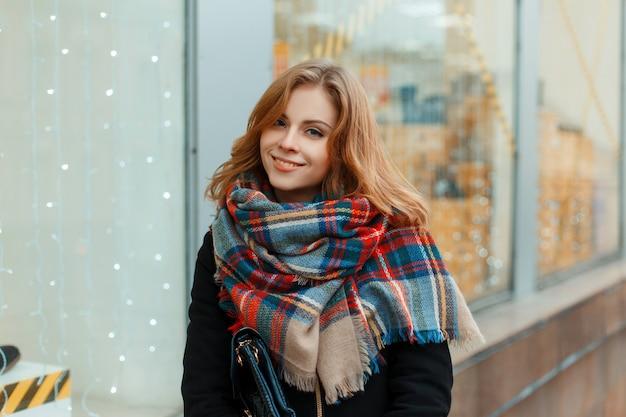 Affascinante giovane donna in un elegante cappotto invernale in guanti neri con una sciarpa di lana vintage è in piedi vicino a una vetrina decorata con una ghirlanda. ragazza allegra cammina per la città