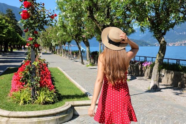 Affascinante giovane donna che cammina lungo la passeggiata fiorita di bellagio sul lago di como, italy