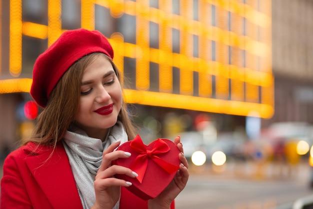 Affascinante giovane donna indossa berretto rosso e cappotto tenendo una scatola regalo a forma di cuore con un fiocco su uno sfondo di luci sfocate. spazio per il testo