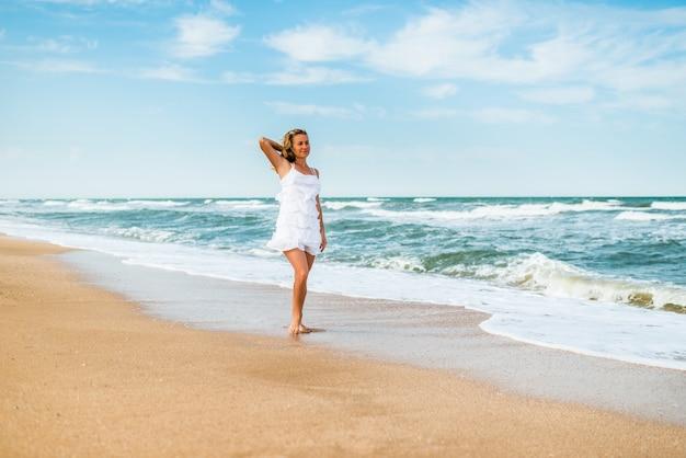 Affascinante giovane donna in un abito bianco cammina lungo le onde del mare calmo sulla costa sabbiosa