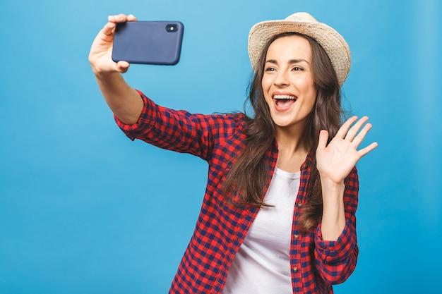 Affascinante giovane donna in viaggio cappello bianco prende selfie