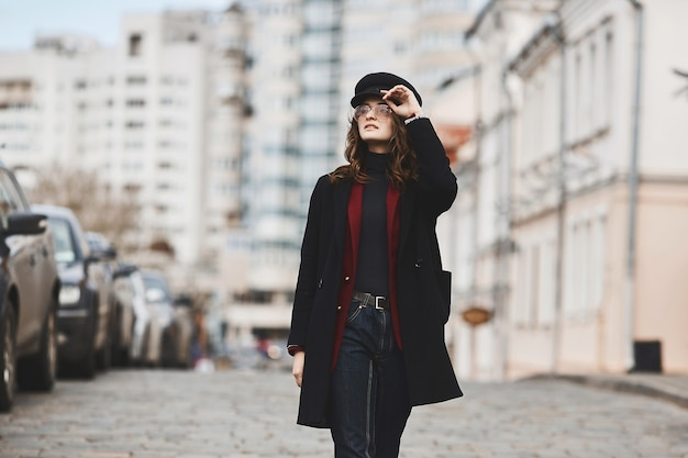 Affascinante giovane donna in un cappotto invernale, cappello alla moda e occhiali da sole, cammina per strada in una grande città. concetto di moda di strada. un posto per il testo, copia spazio.
