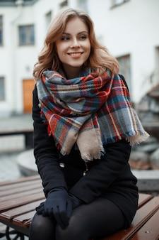 Affascinante giovane donna con un bel sorriso in eleganti vestiti caldi è seduta su una panca in legno e sorridente