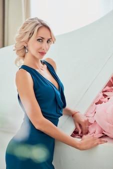 Affascinante giovane donna con acconciatura elegante e vestito alla moda in posa