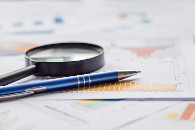 Carta da grafici e grafici, lente d'ingrandimento e penna. finanziario, contabilità, statistica