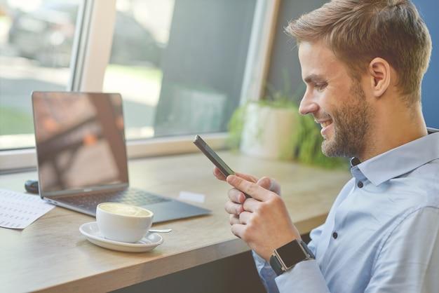 Chiacchierando con gli amici vista laterale di un libero professionista o uomo d'affari usando il suo smartphone e sorridendo