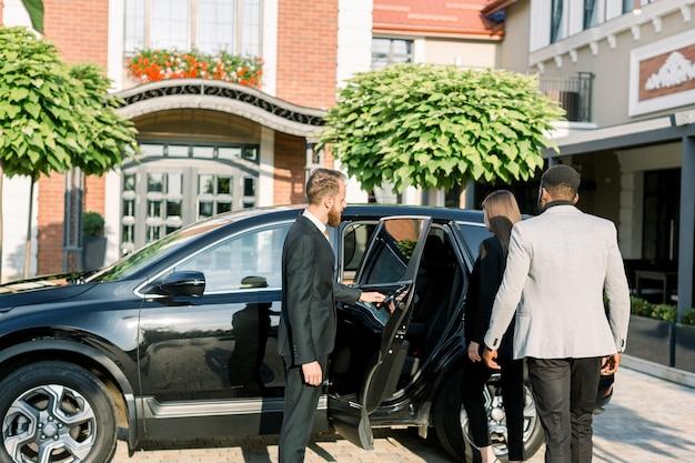 Chauffeur uomo apertura portiera per coppia di affari, donna caucasica e uomo africano, vista laterale. viaggio di lavoro in auto.