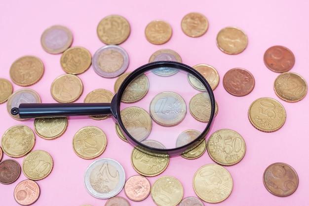 Controlla le monete con una lente d'ingrandimento su uno sfondo rosa. monete in euro attraverso una lente di ingrandimento.