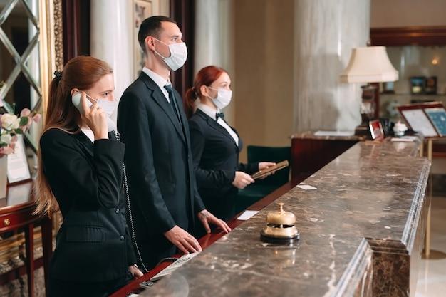 Check in hotel. receptionist al bancone in hotel che indossa maschere mediche come precauzione contro i virus. giovane donna in viaggio d'affari che fa il check-in in hotel
