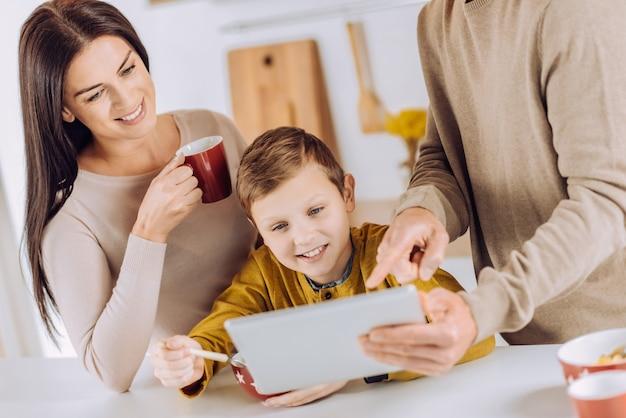 Controlla. ragazzino allegro che mangia la sua colazione e guarda un video su tablet suo padre che lo mostra mentre la madre beve il caffè